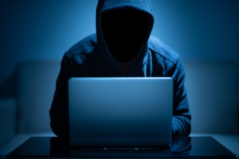 Hooded man with face covered working on a laptop to steal someone's identity